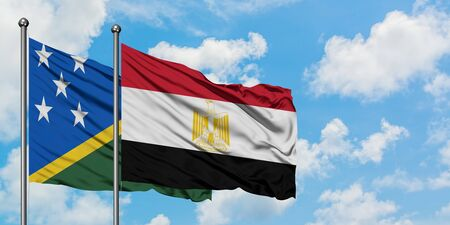 Solomon Islands and Egypt flag waving in the wind against white cloudy blue sky together. Diplomacy concept, international relations.