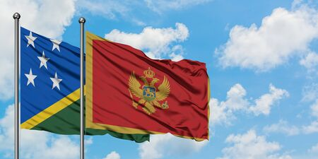 Solomon Islands and Montenegro flag waving in the wind against white cloudy blue sky together. Diplomacy concept, international relations.