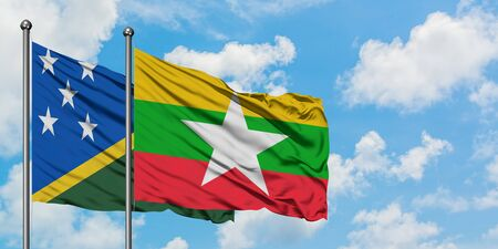 Solomon Islands and Myanmar flag waving in the wind against white cloudy blue sky together. Diplomacy concept, international relations.