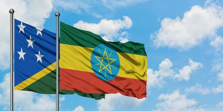 Solomon Islands and Ethiopia flag waving in the wind against white cloudy blue sky together. Diplomacy concept, international relations.
