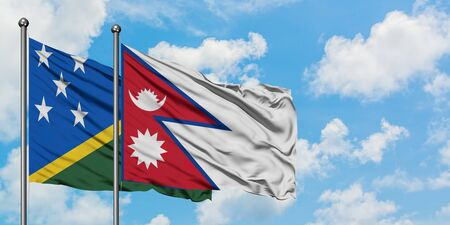 Solomon Islands and Nepal flag waving in the wind against white cloudy blue sky together. Diplomacy concept, international relations.