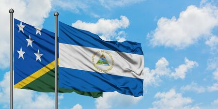 Solomon Islands and Nicaragua flag waving in the wind against white cloudy blue sky together. Diplomacy concept, international relations.