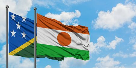 Solomon Islands and Niger flag waving in the wind against white cloudy blue sky together. Diplomacy concept, international relations. Stok Fotoğraf