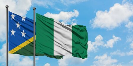 Solomon Islands and Nigeria flag waving in the wind against white cloudy blue sky together. Diplomacy concept, international relations.