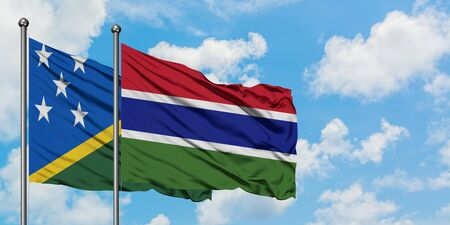 Solomon Islands and Gambia flag waving in the wind against white cloudy blue sky together. Diplomacy concept, international relations. Stok Fotoğraf