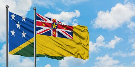 Solomon Islands and Niue flag waving in the wind against white cloudy blue sky together. Diplomacy concept, international relations.
