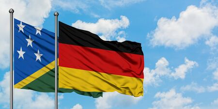 Solomon Islands and Germany flag waving in the wind against white cloudy blue sky together. Diplomacy concept, international relations.