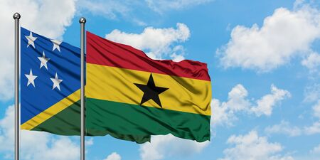 Solomon Islands and Ghana flag waving in the wind against white cloudy blue sky together. Diplomacy concept, international relations.