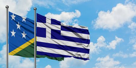 Solomon Islands and Greece flag waving in the wind against white cloudy blue sky together. Diplomacy concept, international relations.