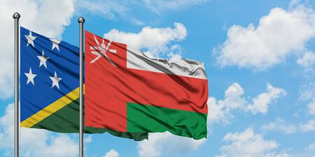 Solomon Islands and Oman flag waving in the wind against white cloudy blue sky together. Diplomacy concept, international relations.