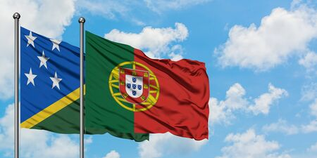 Solomon Islands and Portugal flag waving in the wind against white cloudy blue sky together. Diplomacy concept, international relations.
