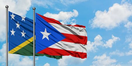 Solomon Islands and Puerto Rico flag waving in the wind against white cloudy blue sky together. Diplomacy concept, international relations.