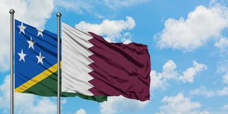 Solomon Islands and Qatar flag waving in the wind against white cloudy blue sky together. Diplomacy concept, international relations.