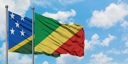 Solomon Islands and Republic Of The Congo flag waving in the wind against white cloudy blue sky together. Diplomacy concept, international relations.