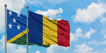 Solomon Islands and Romania flag waving in the wind against white cloudy blue sky together. Diplomacy concept, international relations.