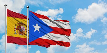 Spain and Puerto Rico flag waving in the wind against white cloudy blue sky together. Diplomacy concept, international relations.