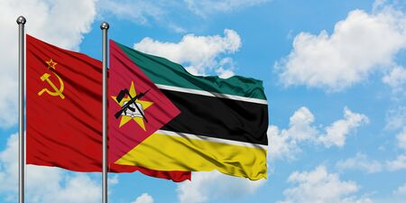 Soviet Union and Mozambique flag waving in the wind against white cloudy blue sky together. Diplomacy concept, international relations.