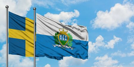 Sweden and San Marino flag waving in the wind against white cloudy blue sky together. Diplomacy concept, international relations. Standard-Bild