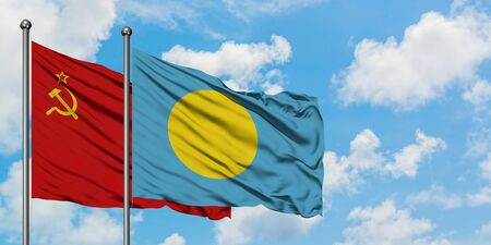 Soviet Union and Palau flag waving in the wind against white cloudy blue sky together. Diplomacy concept, international relations.