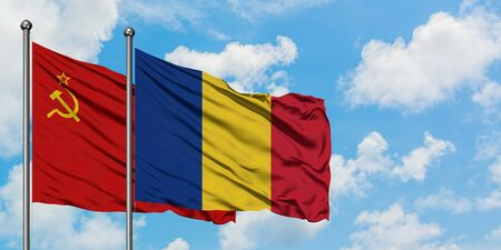 Soviet Union and Romania flag waving in the wind against white cloudy blue sky together. Diplomacy concept, international relations.