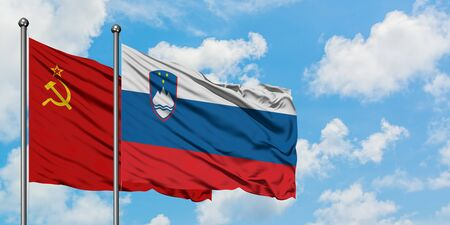 Soviet Union and Slovenia flag waving in the wind against white cloudy blue sky together. Diplomacy concept, international relations.
