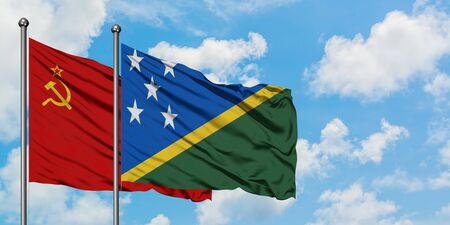 Soviet Union and Solomon Islands flag waving in the wind against white cloudy blue sky together. Diplomacy concept, international relations.