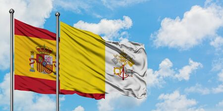 Spain and Vatican City flag waving in the wind against white cloudy blue sky together. Diplomacy concept, international relations.