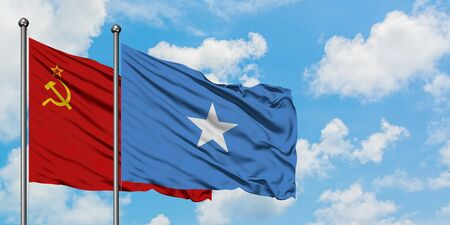 Soviet Union and Somalia flag waving in the wind against white cloudy blue sky together. Diplomacy concept, international relations.