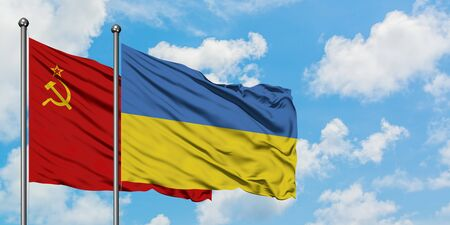 Soviet Union and Ukraine flag waving in the wind against white cloudy blue sky together. Diplomacy concept, international relations.