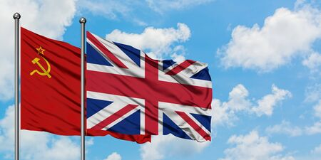 Soviet Union and United Kingdom flag waving in the wind against white cloudy blue sky together. Diplomacy concept, international relations.