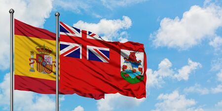 Spain and Bermuda flag waving in the wind against white cloudy blue sky together. Diplomacy concept, international relations.