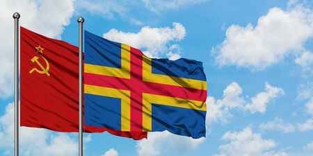 Soviet Union and Aland Islands flag waving in the wind against white cloudy blue sky together. Diplomacy concept, international relations.