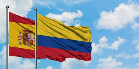 Spain and Colombia flag waving in the wind against white cloudy blue sky together. Diplomacy concept, international relations.