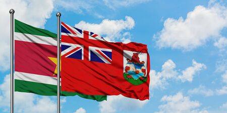 Suriname and Bermuda flag waving in the wind against white cloudy blue sky together. Diplomacy concept, international relations.