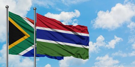 South Africa and Gambia flag waving in the wind against white cloudy blue sky together. Diplomacy concept, international relations.