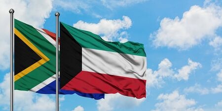 South Africa and Kuwait flag waving in the wind against white cloudy blue sky together. Diplomacy concept, international relations.