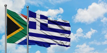 South Africa and Greece flag waving in the wind against white cloudy blue sky together. Diplomacy concept, international relations.