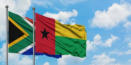 South Africa and Guinea Bissau flag waving in the wind against white cloudy blue sky together. Diplomacy concept, international relations.