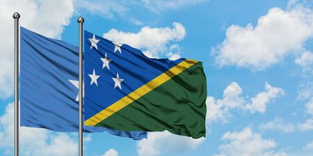 Somalia and Solomon Islands flag waving in the wind against white cloudy blue sky together. Diplomacy concept, international relations.