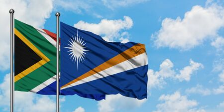 South Africa and Marshall Islands flag waving in the wind against white cloudy blue sky together. Diplomacy concept, international relations. 스톡 콘텐츠