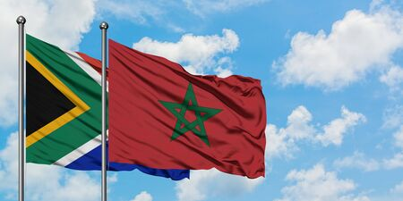 South Africa and Morocco flag waving in the wind against white cloudy blue sky together. Diplomacy concept, international relations.