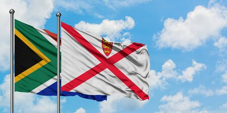 South Africa and Jersey flag waving in the wind against white cloudy blue sky together. Diplomacy concept, international relations.
