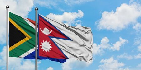 South Africa and Nepal flag waving in the wind against white cloudy blue sky together. Diplomacy concept, international relations. 스톡 콘텐츠