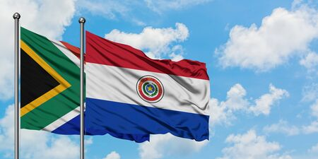 South Africa and Paraguay flag waving in the wind against white cloudy blue sky together. Diplomacy concept, international relations.