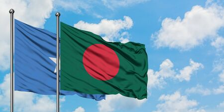 Somalia and Bangladesh flag waving in the wind against white cloudy blue sky together. Diplomacy concept, international relations. Stock Photo