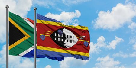South Africa and Swaziland flag waving in the wind against white cloudy blue sky together. Diplomacy concept, international relations.
