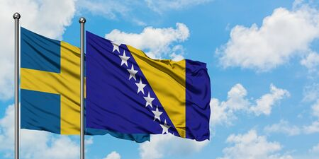 Sweden and Bosnia Herzegovina flag waving in the wind against white cloudy blue sky together. Diplomacy concept, international relations. Standard-Bild