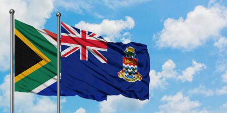 South Africa and Cayman Islands flag waving in the wind against white cloudy blue sky together. Diplomacy concept, international relations. 스톡 콘텐츠