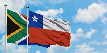 South Africa and Chile flag waving in the wind against white cloudy blue sky together. Diplomacy concept, international relations. 스톡 콘텐츠