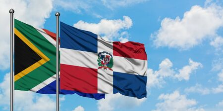 South Africa and Dominican Republic flag waving in the wind against white cloudy blue sky together. Diplomacy concept, international relations.